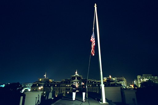 U.S. Marines lower the American flag flying over the White House to half staff at midnight Tuesday, September 10, to mark the anniversary of September 11. Pictured in the background is the Eisenhower Executive Office Building. White House photo by Tina Hager.