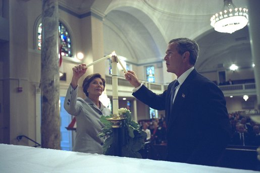 President George W. Bush and First Lady Laura Bush light a candle at St. John Episcopal Church in Washington, D.C., during a private service of prayer and remembrance Wednesday morning, September 11, 2002. White House photo by Eric Draper.