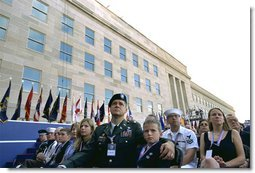 "Sitting in front of the rebuilt section of the Pentagon, service personnel and families listen to President George W. Bush at the Pentagon Observance Wednesday, Sept. 11. ""One year ago, men and women and children were killed here because they were Americans. And because this place is a symbol to the world of our country's might and resolve,"" said the President. ""Today, we remember each life. We rededicate this proud symbol and we renew our commitment to win the war that began here."" White House photo by Eric Draper."