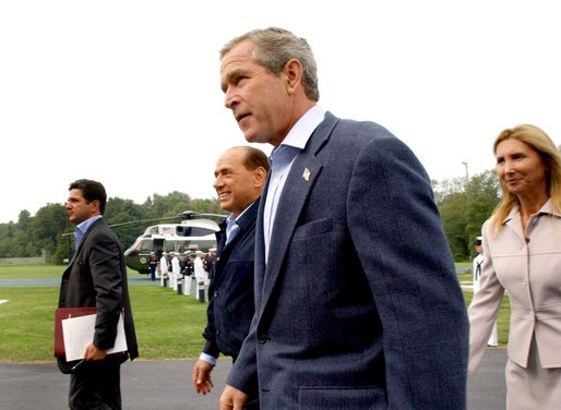 Flanked by interpreters, President George W. Bush and Italian Prime Minister Silvio Berlusconi leave a news conference after Berlusconi's arrival at Camp David, Saturday, Sept. 14, 2002. White House photo by Eric Draper.