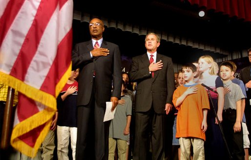 President George W. Bush pledges allegiance to the flag with Secretary of Education Rod Paige at a Pledge Across America event at East Literate Magnet School in Nashville, Tennessee on Tuesday, Sept. 17, 2002.