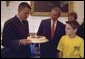 President George W. Bush and Matthew Skowronski, 13, a leukemia survivor, (right), admire the cake Lance Armstrong was given by the White House in honor of his 31st birthday. Armstrong, a cancer survivor and 4-time winner of the Tour De France, spoke Wednesday, Sept. 18, to encourage and support new cancer survivorship initiatives and legislation. White House photo by Paul Morse