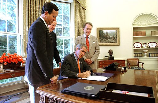 President George W. Bush signs The Flight 93 National Memorial Act in the Oval Office Tuesday, Sept. 24. The bill authorizes the building of a national memorial to the passengers and crew who died aboard Flight 93 when it crashed into Shanksville, Pa., during the Sept. 11 terrorist attacks. Standing with the President are Pennsylvania Congressman Sen. Rick Santorum, far left; Rep. John Murtha, center; and Sen. Arlen Specter. White House photo by Tina Hager.