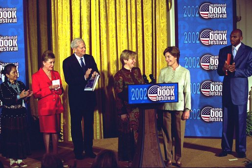 Laura Bush welcomes Ludmila Putina, wife of Vladimir Putin, President of the Russian Federation, to the Second Annual National Book Festival Saturday, October 12, 2002 in the East Room of the White House. Standing with the First Ladies on stage are, left to right, Native American poet Lucy Tapahoso, writer Mary Higgins Clark , Librarian of Congress Director James Billington and NBA player Jerry Stackhouse. White House photo by Susan Sterner.
