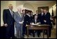 President George W. Bush signs the Sudan Peace Act in the Roosevelt Room at the White House, Oct. 21, 2002. Standing with the President are lawmakers and the Secretary of State Colin Powell, far left, and former Senator and special envoy for peace to the Sudan John Danforth, second from right.