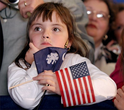 Holding the colors of South Carolina and America, a young girl listens to President George W. Bush during the South Carolina Welcome in Columbia, S.C., Thursday, Oct. 24. White House photo by Eric Draper.