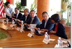 President George W. Bush speaks with National Security Advisor Condoleezza Rice at the start of the group meeting with ASEAN leaders 10th APEC leaders meeting in Los Cabos, Mexico, Saturday, Oct. 26, 2002. Also pictured seated from left are His Majesty Sultan Haji Hassanal Bolkiah Mu'Izzaddin Waddaulah and Pehin Dato Lim Jock Seng both of Brunei and Chief of Staff Andy Card. White House photo by Tina Hager.