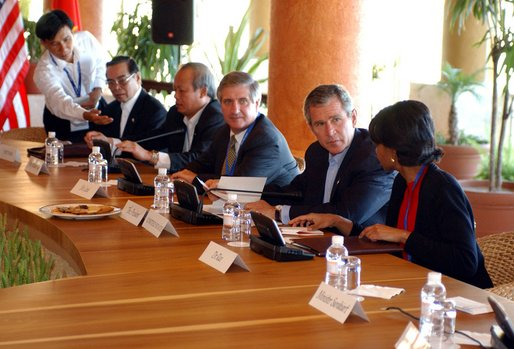 President George W. Bush speaks with National Security Advisor Condoleezza Rice at the start of the group meeting with ASEAN leaders 10th APEC leaders meeting in Los Cabos, Mexico, Saturday, Oct. 26, 2002. Also pictured seated from left are His Majesty Sultan Haji Hassanal Bolkiah Mu'Izzaddin Waddaulah and Pehin Dato Lim Jock Seng both of Brunei and Chief of Staff Andy Card.