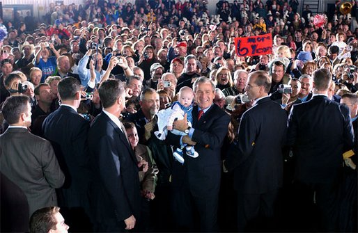 President George W. Bush poses with a baby while greeting the crowd during the Indiana Welcome at the South Bend Regional Airport in South Bend, Ind., Oct. 31. White House photo by Tina Hager.