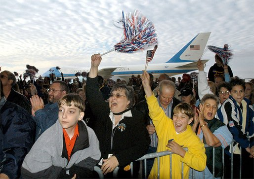 Air Force One stands at the ready for President George W. Bush as a crowd cheers while the aircraft's chief passenger speaks during the Arkansas Welcome at the Northwest Arkansas Regional Airport, Monday, Nov. 4. White House photo by Eric Draper.