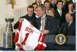 Receiving a jersey from team captain Steve Yzerman, President George W. Bush welcomes the Detroit Red Wings, winners of the NHL 2002 Stanley Cup Championship, to the East Room of the White House Friday, Nov. 8.  White House photo by Paul Morse