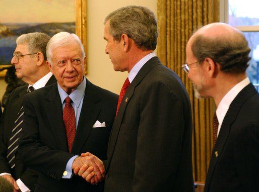 "President George W. Bush greets former President Jimmy Carter during a photo opportunity in the Oval Office with the Nobel Laureates Monday, Nov.18. ""These Americans are a great honor to their fields and a great honor to our country. And we're proud to have you here. We're proud for what you've done, for not only America but the world. And we're proud for your contributions,"" said President Bush. White House photo by Tina Hager."