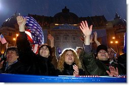 "Braving a cold rain, thousands of Romanian citizens came to Revolution Square to hear President Bush speak Nov. 23. ""I know that your hardship did not end with your oppression. America respects your labor, your patience, your daily determination to find a better life. Your effort has been recognized by an offer to NATO membership. We welcome Romania into NATO,"" said President Bush.  White House photo by Paul Morse"