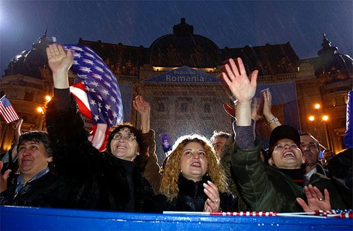 "Braving a cold rain, thousands of Romanian citizens came to Revolution Square to hear President Bush speak Nov. 23. ""I know that your hardship did not end with your oppression. America respects your labor, your patience, your daily determination to find a better life. Your effort has been recognized by an offer to NATO membership. We welcome Romania into NATO,"" said President Bush. White House photo by Paul Morse."