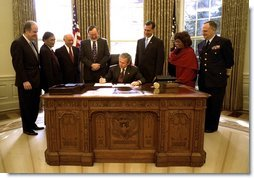 President George W. Bush signs the Maritime Transportation Security Act of 2002 in the Oval Office, Nov. 25, 2002.  White House photo by Paul Morse