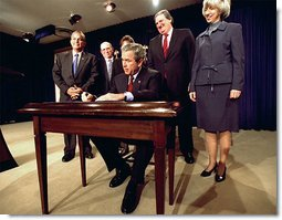 President George W. Bush signs H.R. 3908, the Reauthorization of the North American Wetlands Conservation Act in the Dwight D. Eisenhower Executive Office Building Dec. 2. Standing with the President for the signing are, from left to right, Rep. Robert Underwood (D-Guam), Rep. Wayne Gilchrest (R-MD), Sec. of Agriculture Ann Veneman, Sen. Bon Smith (R-NH) and Sec of Interior Gale Norton. The legislation matches federal funds with non-federal sources to promote public-private partnerships that conserve and restore the nation's wetlands.  White House photo by Tina Hager