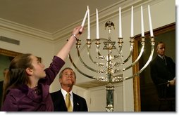 President George W. Bush watches as Daniella Wald, 12, lights one of the candles on the Menorah Wednesday, Dec 4 in the White House. President Bush presented one of the lighted candles to Daniella Wald, who lit the first three candles, and she presented the lighter candle to her sister, Alexandra Wald, 15, who lit the other three. Both of the girls are from Manhattan, and their father, Victor Wald, was killed in the Sept. 11 attacks on the World Trade Center.  White House photo by Paul Morse