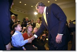 President George W. Bush talks to Solveig Haugen, her twin sister Liv and their younger brother Tad, after the signing of the Dot Kids Implementation and Efficiency Act of 2002 in the Roosevelt Room, Dec 4. The Haugen family of Loudoun County, Virginia is one family that will benefit from the act. The bill creates a second level Internet domain (kids.us), within the United States country code, that will provide a safe online environment for children ages 13 and under.  White House photo by Eric Draper