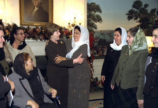 Afghani teacher Rayhaanah of Kabul embraces Laura Bush during a visit of 13 Afghani women teachers to the White House Wednesday, December 4, 2002. The teachers are concluding a six-week training program in the United States to help them become master teachers and teacher trainers upon return to Afghanistan. White House photo by Susan Sterner