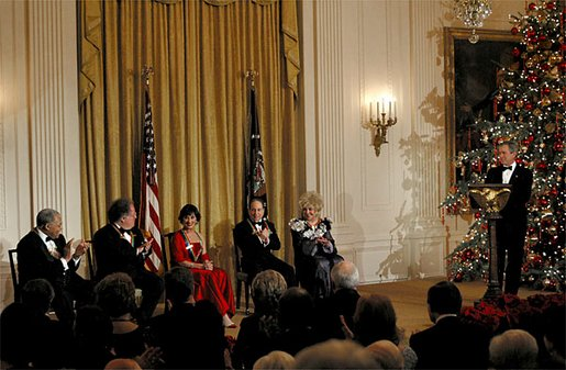 President George W. Bush welcomes the recipients of the Kennedy Center Honors of 2002 to the White House Sunday, Dec. 8. Each year The John F. Kennedy Center for the Performing Arts honors a select number of artists for lifetime achievements and their influence upon American culture. From left to right, the recipients are actor James Earl Jones; conductor James Levine; dancer and actress Chita Rivera; singer Paul Simon and actress Elizabeth Taylor. White House photo by Susan Sterner.