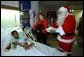 Laura Bush is accompanied by her Scottish Terrier, Barney, and Santa Claus as she visits Brittanie Morris at the Children's National Medical Center in Washington, D.C., Thursday, December 12, 2002. After spending time with children on the neurology and orthopedic units, Mrs. Bush hosted the annual children's Christmas program, during which she debuted a video tour of the White House Christmas decorations from Barney's perspective. White House photo by Susan Sterner.