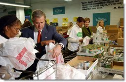 "President George W. Bush and Laura Bush help volunteers pack food during their visit to the Capital Area Food Bank in Washington, D.C., Thursday, Dec. 19. ""More Americans need to volunteer. There are ways to do so. The USAFreedomCorps.gov on the web page is the place to look,"" said the President in his remarks. ""You can call 1-877-USA-CORPS and find out ways that you can help. If you are interested in being a part of feeding those who hunger, this is a great place to come to.""  White House photo by Tina Hager"