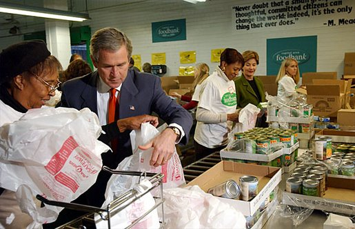 "President George W. Bush and Laura Bush help volunteers pack food during their visit to the Capital Area Food Bank in Washington, D.C., Thursday, Dec. 19. ""More Americans need to volunteer. There are ways to do so. The USAFreedomCorps.gov on the web page is the place to look,"" said the President in his remarks. ""You can call 1-877-USA-CORPS and find out ways that you can help. If you are interested in being a part of feeding those who hunger, this is a great place to come to."" White House photo by Tina Hager."
