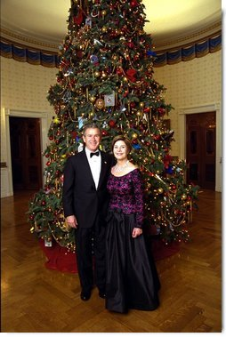 President George W. Bush and Laura Bush stand before the Blue Room Christmas Tree Sunday, December 8, 2002 prior to hosting a reception for the Kennedy Center Honorees. Mrs. Bush is wearing a floor length gown designed by Arnold Scaasi.  White House photo by Eric Draper
