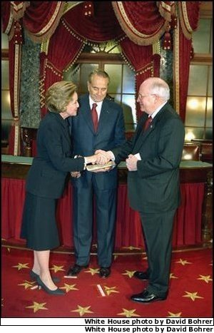 In his role as President of the Senate, Vice President Dick Cheney presides over the swearing in of 35 new senators as part of the opening of the 108th Congress Tuesday Jan. 7, 2003. Here, the Vice President congratulates newly-elected Senator Elizabeth Dole, R-N.C., in the Old Senate Chamber of the Capitol as her husband, former Senator Bob Dole, looks on. White House photo by David Bohrer.