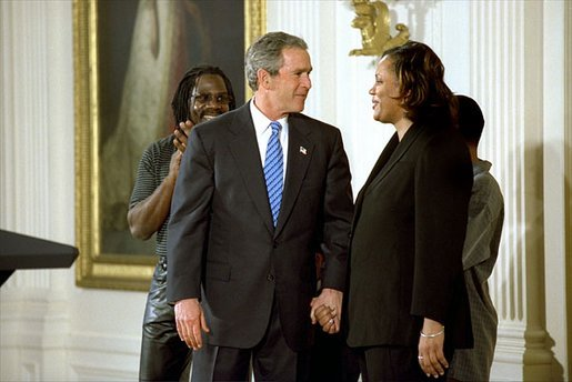 President George W. Bush congratulates Pamela Hedrick during a ceremony honoring graduates of welfare-to-work programs in the East Room. Ms. Hedrick was on public assistance for eight years in Columbus, Ohio, before volunteering at the Greenbriar Enrichment Center, where she organized a women's support group and received job training. The President's Council of Economic Advisers (CEA) estimates the Jobs and Growth plan will create 1.4 million new jobs by the end of 2004. White House photo by Tina Hager.