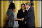 Talking with Dante Nelms, 12, President George W. Bush greets Dante's mother, Pamela Hedrick, right, her husband, Martia Jackson, and her son Darius McIver, 5,(not pictured) during a program honoring graduates of welfare-to-work programs in the East Room Tuesday, Jan. 14, 2003. Ms. Hedrick was on public assistance for eight years in Columbus, Ohio, before volunteering at the Greenbriar Enrichment Center, where she organized a women's support group and received job training. White House photo by Paul Morse.