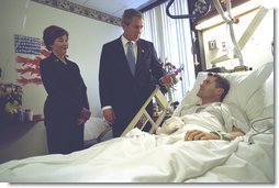 President George W. Bush and First Lady Laura Bush visit with Army Staff Sergeant Michael McNaughton, of Denham Springs, Louisiana, at Walter Reed Army Medical Center in Washington, D.C., Friday, January 17, 2003. Sergeant McNaughton was wounded on January 9 in Afghanistan. The First Couple visited four other wounded soldiers at the hospital.  White House photo by Eric Draper