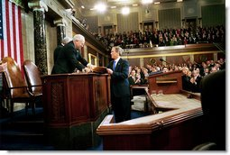 President George W. Bush hands Vice President Dick Cheney and Speaker of the House Dennis Hastert (not pictured) a copy of his State of the Union Address upon his arrival to the House Chamber at the U.S. Capitol Tuesday, Jan. 28, 2003.   White House photo by Eric Draper