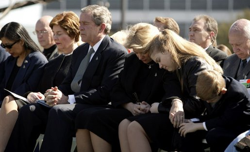 Joining the family of Space Shuttle Columbia Commander Rick Husband, President George W. Bush and Laura Bush bow their heads in prayer during a memorial service at NASA's Lyndon B. Johnson Space Center Tuesday, Feb. 4, 2003. Sitting with the President are Mr. Husband's wife, Evelyn, and children Laura and Matthew. White House photo by Paul Morse