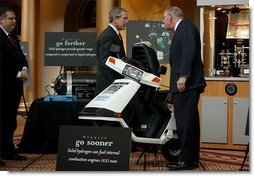 "President George W. Bush looks over a scooter powered by solid hydrogen fuel during a demonstration of energy technologies at The National Building Museum in Washington, D.C., Thursday, Feb. 6, 2003. ""Cars that will run on hydrogen fuel produce only water, not exhaust fumes,"" said the President in his remarks. ""If we develop hydrogen power to its full potential, we can reduce our demand for oil by over 11 million barrels per day by the year 2040.""  White House photo by Paul Morse"
