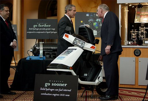 "President George W. Bush looks over a scooter powered by solid hydrogen fuel during a demonstration of energy technologies at The National Building Museum in Washington, D.C., Thursday, Feb. 6, 2003. ""Cars that will run on hydrogen fuel produce only water, not exhaust fumes,"" said the President in his remarks. ""If we develop hydrogen power to its full potential, we can reduce our demand for oil by over 11 million barrels per day by the year 2040."" White House photo by Paul Morse."