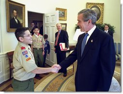 President George W. Bush talks with First Class Scout Zachary Gomez before the presentation of the annual report by the Boy Scouts of America in the Oval Office Tuesday, Feb. 11, 2003. In 1911, President William Howard Taft was the first President to host a visit by the BSA. Every President since then has served as Honorary President of the BSA during his term. White House photo by Eric Draper.