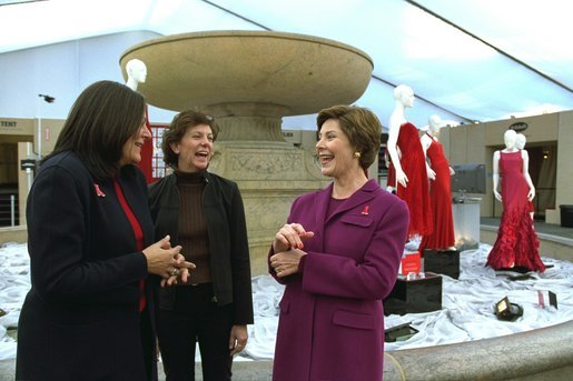 "Laura Bush shares a light moment with Fern Mallis of 7th on Sixth, left, and Lynn Long, chief of Fashion Week production, after reviewing the designer dresses on display for ""The Red Dress Project"" in Bryant Park in New York City Friday, Feb. 14, 2003. ""The Red Dress Project"" is part of the Heart Truth campaign to raise awareness of heart disease as the number one killer of women. The dresses were created by 19 American designers and will tour for one year and then be auctioned to benefit the American Heart Association. White House photo by Susan Sterner."