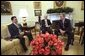 President George W. Bush meets with Yasar Yakis, Foreign Minister of Turkey, center, and Ali Babacan, Minister of State for the Economy of Turkey, in the Oval Office Friday, Feb. 14, 2003. White House photo by Tina Hager