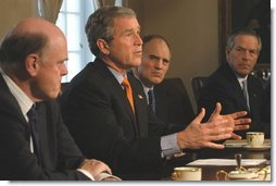 As Treasury Secretary John Snow, left, Director of National Economic Council Stephen Friedman, center, and Commerce Secretary Don Evans sit by his side, President George W. Bush takes a few questions from the media during a meeting with the National Economic Council in the Cabinet Room Tuesday, Feb. 25, 2003.  White House photo by Eric Draper