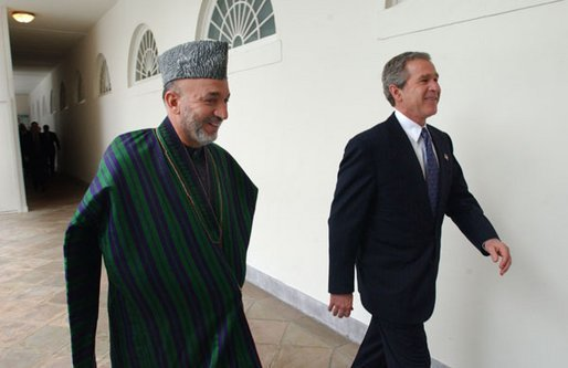 President George W. Bush and President Hamid Karzai of Afghanistan walk through the colonnade after meeting in the Oval Office Thursday, Feb. 27, 2003. White House photo by Tina Hager.