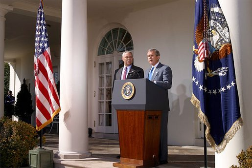 As Secretary of State Colin Powell stands by his side, President George W. Bush addresses the media in the Rose Garden Friday, March 14, 2003. White House photo by Paul Morse