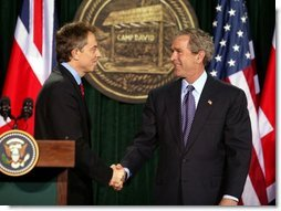 "President George W. Bush and British Prime Minister Tony Blair shake hands after they conclude a joint news conference at the Camp David, March 27, 2003. ""The United States and United Kingdom are acting together in a noble purpose. We're working together to make the world more peaceful; we're working together to make our respective nations and all the free nations of the world more secure; and we're working to free the Iraqi people,"" President Bush said.  White House photo by Paul Morse"