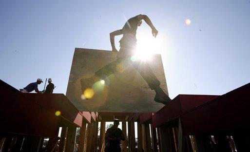 A marine helps construct the stage at the event site where President George W. Bush will address the troops Thursday at Camp Lejeune in Jacksonville, N.C., Wednesday, April 2, 2003. White House photo by Paul Morse.