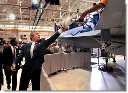 President George W. Bush reaches for a cap to sign after speaking at the Boeing F-18 Production Facility in St. Louis, Mo., Wednesday, April 16, 2003.  White House photo by Eric Draper