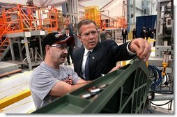 President George W. Bush inspects an F-18 part with Boeing Employee Rocky Mayberry during a tour of the Boeing F-18 Production Facility in St. Louis, Mo., Wednesday, April 16, 2003.  White House photo by Eric Draper