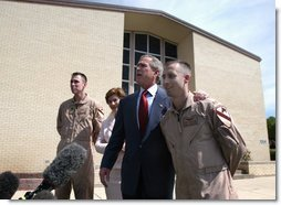 President George W. Bush puts his arm around Chief Warrant Officer David S. Williams as he speaks to the media with Chief Warrant Officer Ronald D. Young Jr., left, and Mrs. Bush after attending Easter church services at the 4th Infantry Division Memorial Chapel at Fort Hood, Sunday, April 20, 2003. Williams and Young are former POW's.  White House photo by Eric Draper