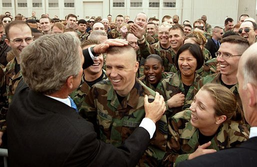 President George W. Bush provides a little touch-up on a soldier's haircut as he greets military personnel at Wright-Patterson Air Force Base in Dayton, Ohio, April 24, 2003. White House photo by Paul Morse