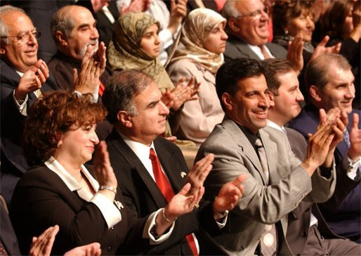 Standing at the far right, Haider Al-Jebori, President of the Steering Committee for Iraqi Home Culture, applauds for President George W. Bush at the Ford Community and Performing Arts Center in Dearborn, Mich., Monday, April 28, 2003. White House photo by Tina Hager