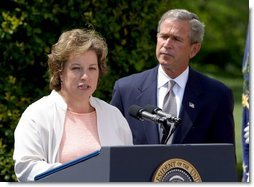 President George W. Bush listens to Betsy Rogers, 2003 National Teacher of the Year, in a ceremony in the East Garden Wednesday, April 30, 2003. Rogers is a 1st and 2nd grade teacher at Leeds Elementary School in Leeds, Ala.  White House photo by Paul Morse